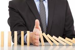 Contínuo dos dominós da parada da mão do homem de negócios ruído Foto de Stock Royalty Free