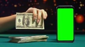 Conta de cem-dólar da exibição da mulher perto do smartphone verde da tela, salário em linha video estoque