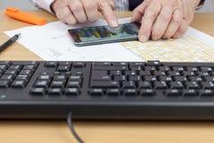 Conta de Finamcial que verifica uma carta em seu telefone esperto Fotografia de Stock Royalty Free
