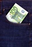 conta do euro 100 no bolso das calças de brim Fotografia de Stock