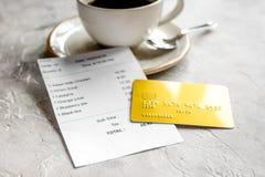 Conta do restaurante que paga pelo cartão de crédito pelo café no fundo de pedra da tabela imagens de stock