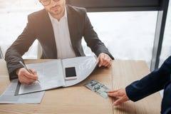 Conta do toque da mão da mulher de 100 dólares na tabela na sala Dá-o para equipar Escreve no caderno e no olhar no dinheiro cort imagens de stock