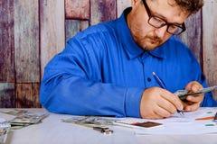Conta o dinheiro e escreve o resultado ? nota Notas de d?lar na tabela que conta c?dulas do d?lar imagens de stock