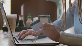 Conta pagando da jovem mulher, compra em linha, introduzindo o número de cartão de crédito Mulher atrativa que paga pela compra e video estoque