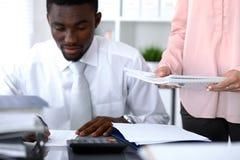 Contabile afroamericano o ispettore finanziario che stendere rapporto, calcolatore o controllante equilibrio Revenu interno fotografie stock