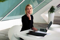 Contabile femminile che parla sul telefono delle cellule prima della preparazione dei rapporti mensili sul computer portatile Fotografia Stock Libera da Diritti