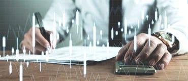 Contabilità dell'uomo d'affari ed analizzare i grafici di investimento Affare immagine stock