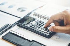 Contabilità finanziaria dell'uomo di affari che calcola investimento economico costato del bilancio e che conserva concetto immagine stock