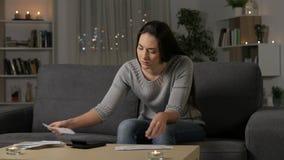 Contabilità triste della donna che controlla le ricevute nella notte video d archivio
