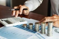 Contable Calculating del hombre de negocios en los documentos y la pila de monedas, la inversi?n de los datos de la pila del dine imagen de archivo libre de regalías