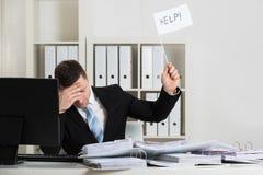 Contable con exceso de trabajo Holding Help Sign en el escritorio fotografía de archivo