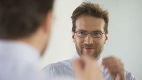 Contable de banco de sexo masculino que intenta sobre los nuevos vidrios, mirando en espejo con sonrisa en cara almacen de metraje de vídeo