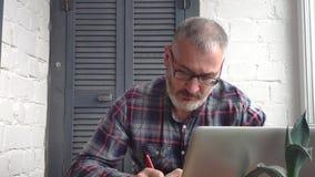 Contable de sexo masculino barbudo canoso que trabaja en casa detrás de un ordenador portátil, haciendo un informe metrajes