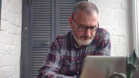 Contable de sexo masculino barbudo canoso que trabaja en casa detrás de un ordenador portátil, haciendo un informe contra el cont almacen de metraje de vídeo