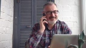 Contable de sexo masculino barbudo canoso que trabaja en casa detrás de un ordenador portátil, haciendo un informe contra el cont metrajes