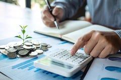 Contable del hombre de negocios que hace notas en el informe que hace finanzas y calcular sobre el coste de la inversión y que an fotografía de archivo