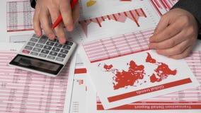 Contable del hombre de negocios que usa la calculadora para calcular finanzas en oficina del escritorio Informes rojos del concep almacen de video