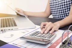 Contable del negocio con el gráfico del documento financiero y la calculadora Imagen de archivo libre de regalías