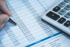 Contable en la contabilidad Hoja de cálculo con la pluma de tenencia humana de la mano y calculadora en azul del negocio Balance  Fotos de archivo libres de regalías