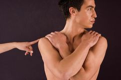 Contact. Woman's finger touching shoulder of man's naked torso Stock Photos