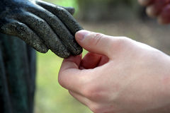 Contact. Statue vs human hand stock image