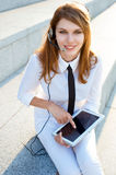 Contact center girl with hands free headset holding digital PC tablet Stock Photo