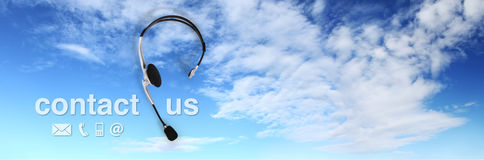 Contact concept , headset on blue sky, and contact us text Royalty Free Stock Images