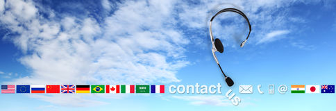 Contact concept , headset with flags on sky, and contact us text Royalty Free Stock Photography