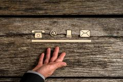 Contact concept with a line of phone, web, mobile and mail icons. Represented by a businessman on rustic wood Royalty Free Stock Photo