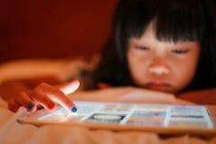 Contact d'astuce de doigt d'enfant sur le dispositif numérique de comprimé photo libre de droits