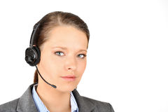 Contact by headset. Black haired woman wearing a headset and a suit ready for a customers call. Very crisp photo with a real focus on the front eye Stock Photography