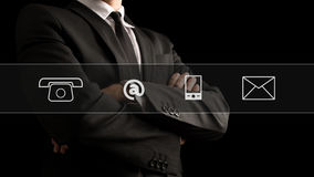Contact icons over businessman crossing arms on front Stock Photo