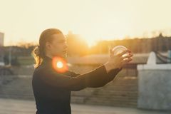 Contact juggling. Boy balances with glass ball on his hands. Glare of setting sun in frame. Skill performance. Trend view Stock Image
