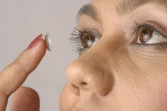 Contact lens. Young woman, close-up, inserting a contact lens in her eye Royalty Free Stock Photography