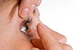 Contact lens. The picture shows woman's face while she inserts a contact lens Stock Images