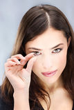 Contact lens. Young woman holding contact lens with two fingers in front of her eye Royalty Free Stock Image