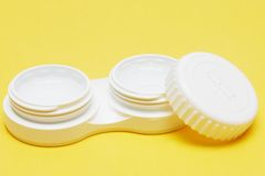 Contact Lens case. With contact lens inside against plain background Stock Images