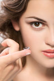 Contact lens. On finger of young woman looking on camera Royalty Free Stock Image