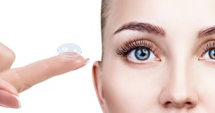 Contact lens on index finger near beautiful female face. royalty free stock image