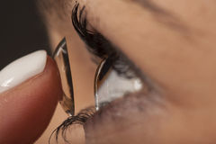 Contact lens. Woman putting on contact lenses royalty free stock images