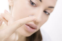Contact lens: Young woman holding contact lens on finger in fron Royalty Free Stock Image