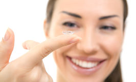 Contact lens: Young woman holding contact lens on finger in fron Royalty Free Stock Images