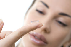 Contact lens: Young woman holding contact lens on finger in fron Royalty Free Stock Photo