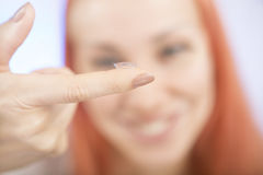 Contact lens: Young woman holding contact lens on finger in fron Royalty Free Stock Photography