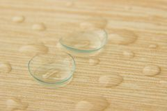 Contact lenses for eyes with drops of solution on a wooden table Stock Photo