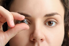 Contact lenses. Contact lens on your finger comes to the eye on a white isolated background Royalty Free Stock Image