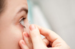 Contact lenses. Woman putting on contact lenses the right way stock image