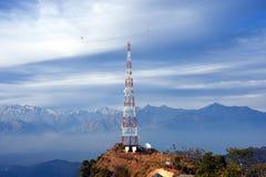 Contact mobiele toren bij hoog heuvelig dorp van Ashapuri in Himachal Pradesh, India met sneeuwbergen in de achtergrond Stock Foto