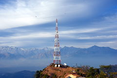 Contact mobile tower at high hilly village of Ashapuri in Himachal Pradesh, India with snow mountains in  the backdrop Stock Photo