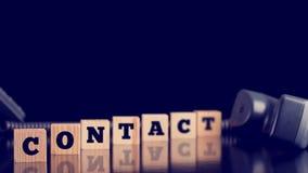 Contact op houten blokken met een telefoonzaktelefoon die alongsid liggen Stock Fotografie